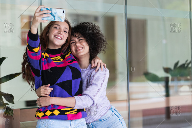 Positive diverse women hugging and taking photo on selfie camera of smartphone while having fun on street