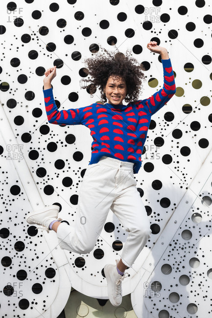 Carefree African American female in stylish outfit and with curly hair in moment of jumping above ground in urban area of city