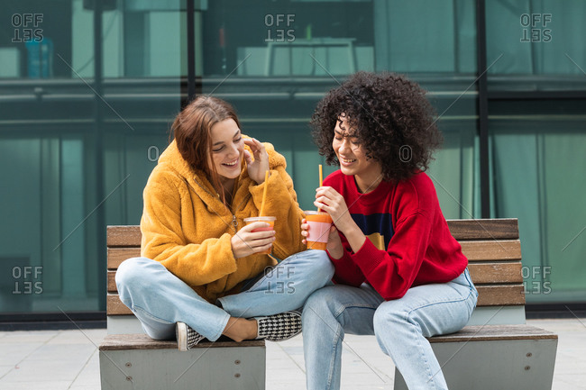Delighted multiethnic female friends in trendy wear sitting on bench in city and drinking sweet juice to go from plastic cups while looking at each other and spending weekend together