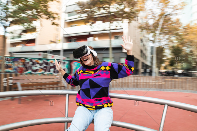 Excited female wearing modern VR glasses experiencing virtual reality while riding roundabout on playground with raised arms