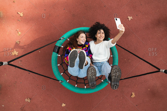 Top view of multiracial female friends lying on net swing on playground and taking selfie on smartphone while spending time together and having fun