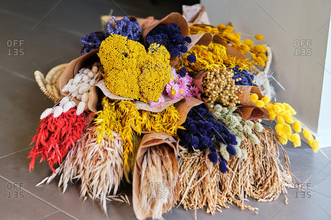 Colorful assorted fresh and dried flowers arranged in bouquets wrapped in craft paper in flower shop