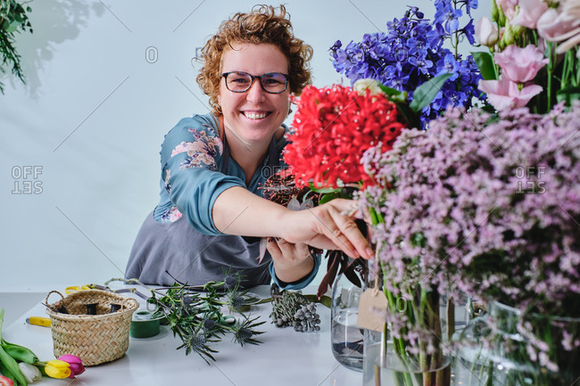Cheerful female florist in apron making bouquet from colorful fresh tulips while working in flower shop looking at camera