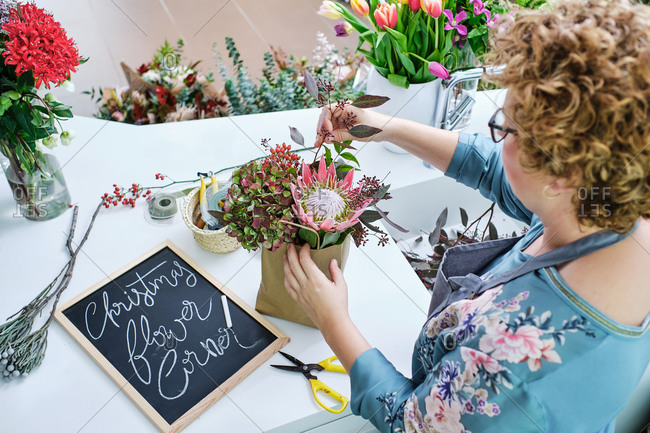 From above of female florist in apron standing in shop and creating bouquet from Hydrangea and King protea flowers