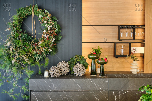 Green natural Christmas wreath and decorative plants arranged on wall and counter in apartment with modern interior for winter holidays