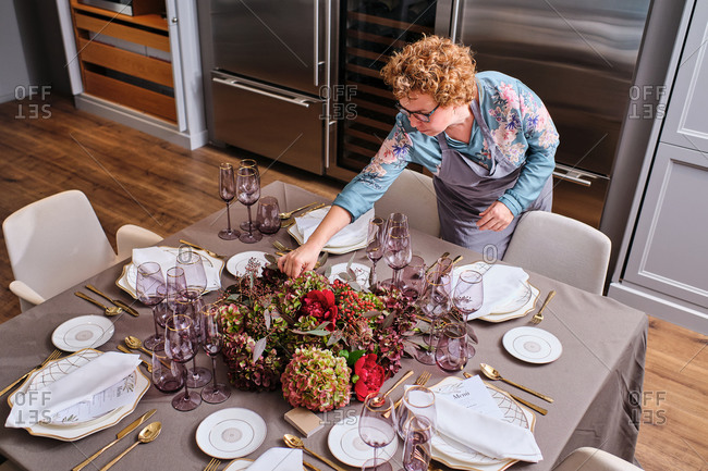 From above of female housewife setting table with delicate flowers for festive event at home