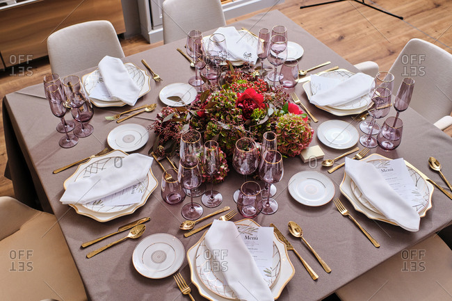 From above of table served with tableware and red flowers at home for celebrating festive event