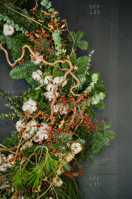 Green natural Christmas wreath and decorative plants arranged on wall in apartment with modern interior for winter holidays