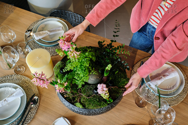 From above cropped unrecognizable female housewife setting table with delicate flowers for festive event at home