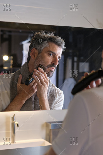 Stock photo of middle age man using beard trimmer in the bathroom.