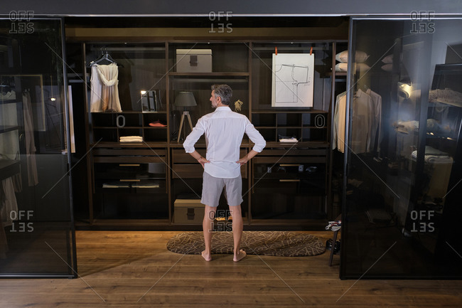 Stock photo of middle aged man choosing clothes for the day in his big dressing room.