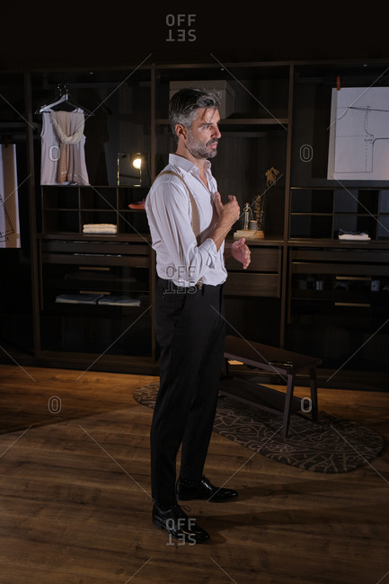 Stock photo of middle aged man adjusting his suspenders in big dressing room.