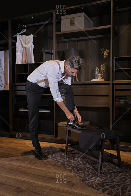 Stock photo of middle aged man dressing up in big dressing room and putting on his shoes.