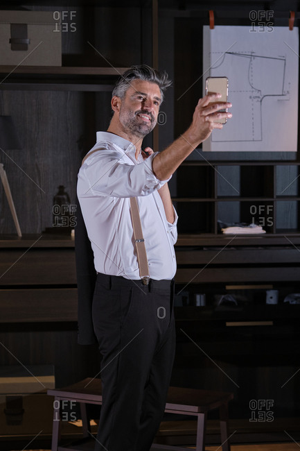 Stock photo of elegant business man wearing suit taking a photo on his phone.
