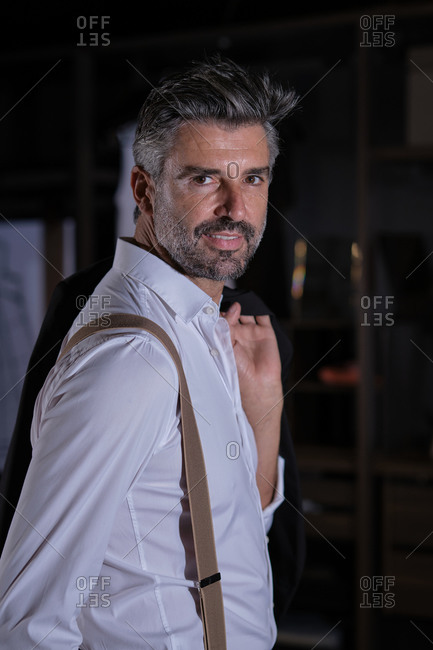 Stock photo of handsome man wearing suit and suspenders smiling and looking at camera.
