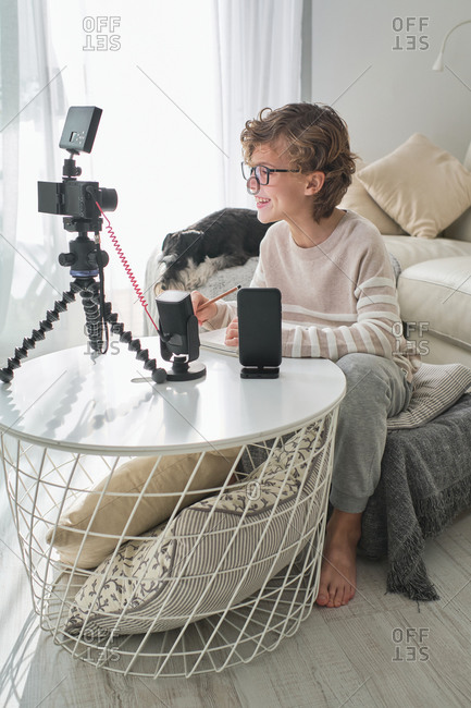 Adorable boy in his living room recording himself with camera.