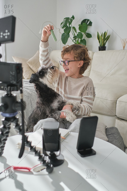 Happy boy playing with his lovely dog and filming a video for his channel.