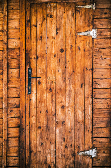 Weathered wooden door of aged cozy residential house located in countryside in daytime