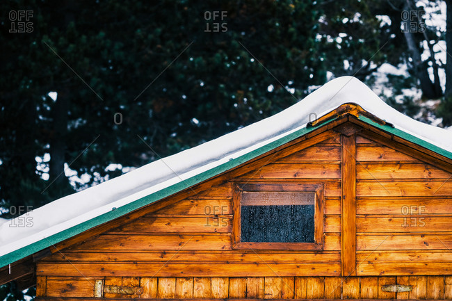 Cozy typical wooden house with snowy roof and small window covered with hoarfrost on winter day
