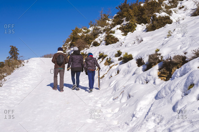 Back view of group of travelers in warm clothes climbing up snowy slope of Matagalls mountain of Montseny Massif in sunny winter day in Spain