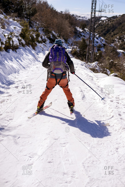 Back view of unrecognizable skier in outerwear walking along snowy trail in winter in Matagalls on sunny day