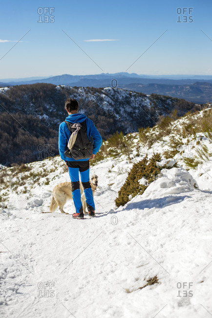 Back view of unrecognizable male backpacker with dog admiring landscape of Montseny Massif while standing on slope of high mountain covered with snow in sunny winter day in Spain