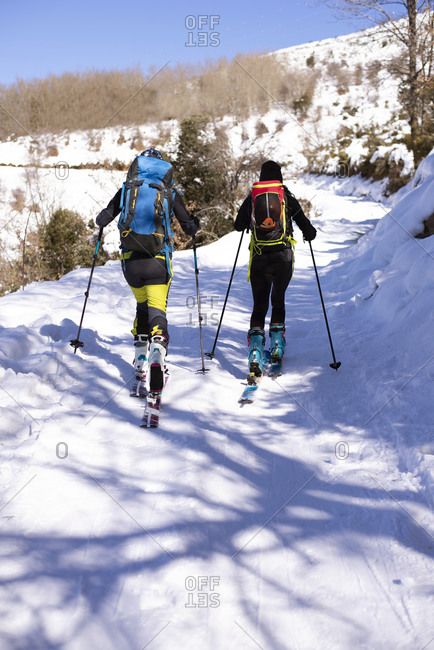 Back view of unrecognizable skiers in outerwear walking along snowy trail in winter in Matagalls on sunny day