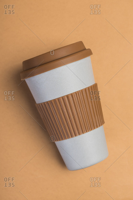 Minimalist white paper cup of takeaway coffee with brown silicone ring and lid against beige background