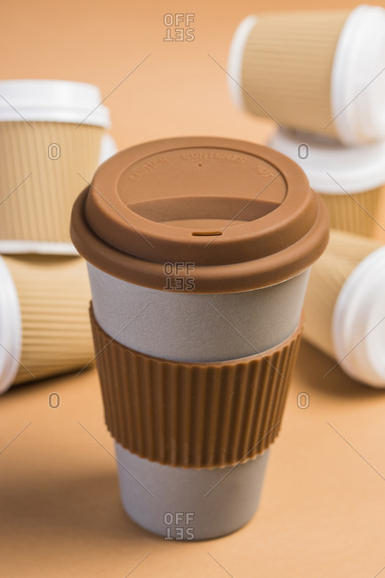 Various disposable cups of hot drinks placed on wooden table in cafe