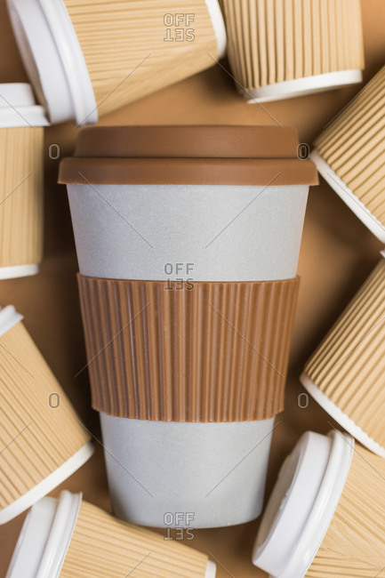 From above of various disposable cups of hot drinks placed on wooden table in cafe