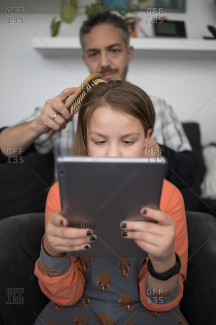 Loving careful adult dad with hairbrush combing hair of daughter using tablet at home