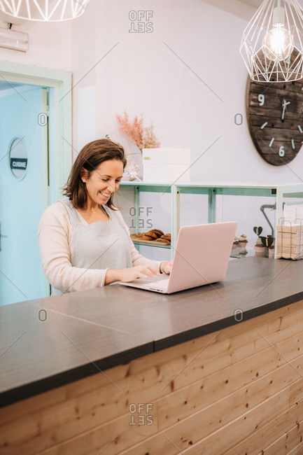 Smiling adult female entrepreneur standing at counter and using laptop while working in cozy cafe