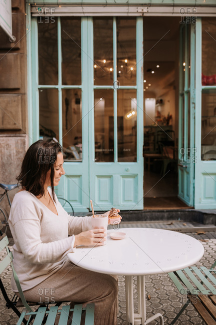 Side view of positive adult female in casual clothes sitting at table on terrace of cozy cafeteria and enjoying frappe coffee and cupcake