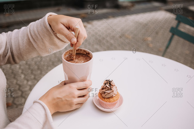 Side view of cropped unrecognizable adult female in casual clothes sitting at table on terrace of cozy cafeteria and enjoying frappe coffee and cupcake