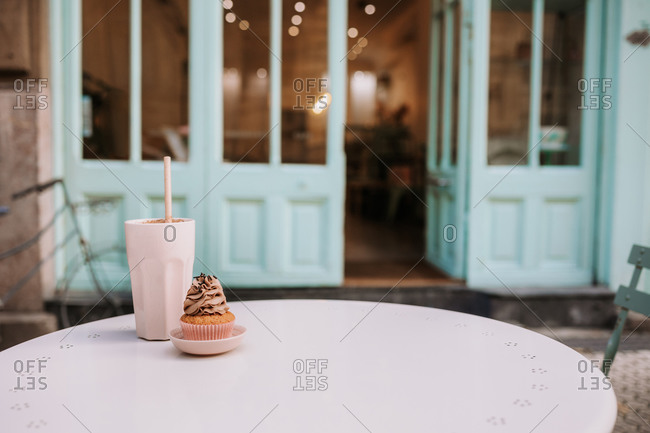 Yummy cupcake and glass of drink served on round table placed on terrace of cozy confectionery cafe