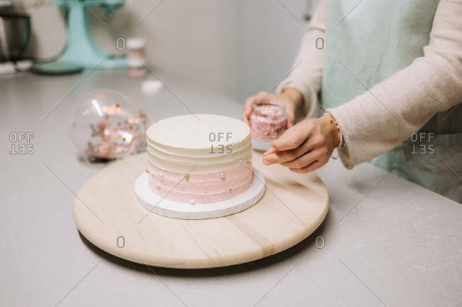 Crop anonymous female confectioner arranging edible pearls on cake covered with cream while working at counter in confectionery