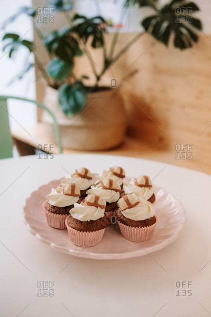 Delectable chocolate cupcakes with whipped cream on plate placed on table