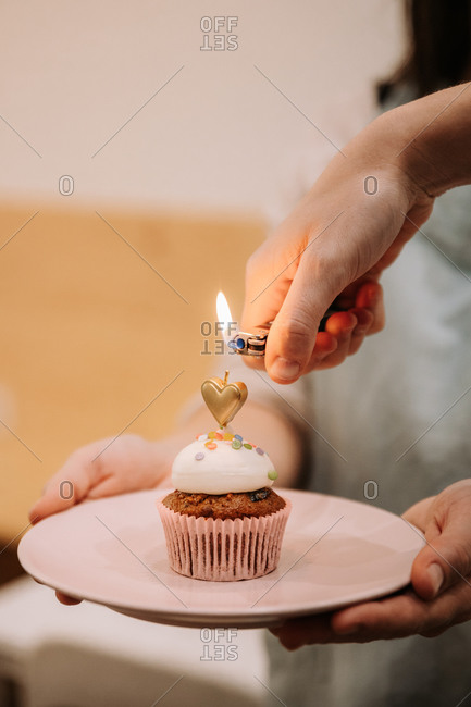 Crop anonymous woman lightning candle on festive cupcake with cream and sprinkles during birthday celebration