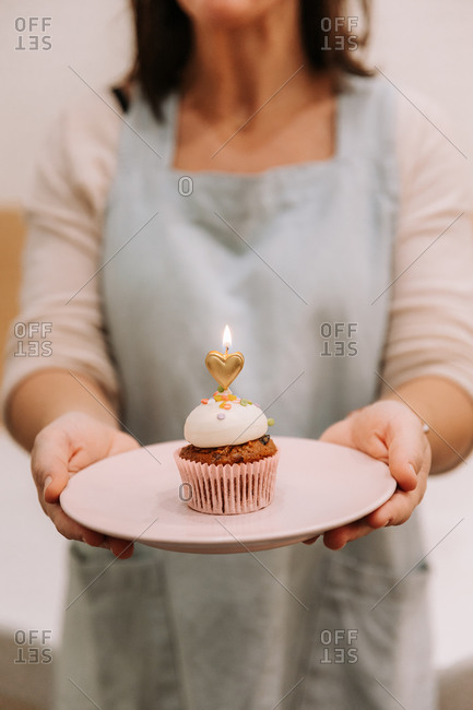 Crop unrecognizable female in apron holding plate with yummy sweet cupcake decorated with burning heart shaped candle