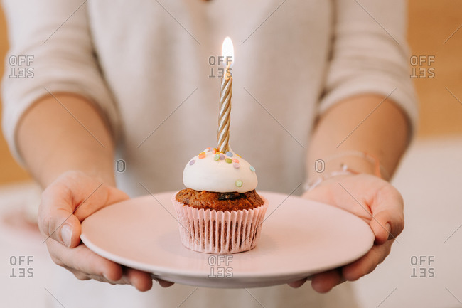 Crop unrecognizable female in apron holding plate with yummy sweet cupcake decorated with burning candle