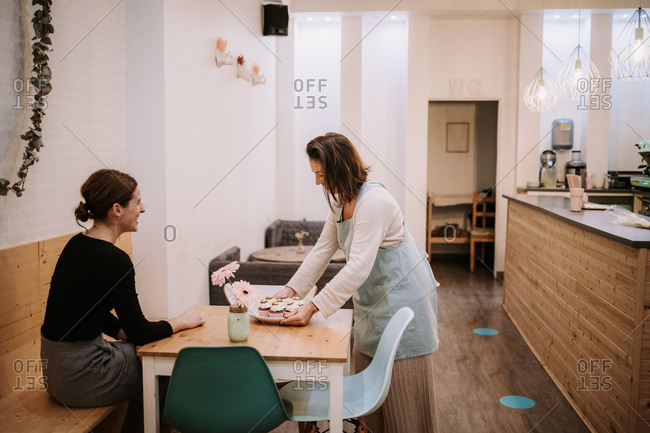 Smiling female small business owner serving delicious cupcake to customer sitting at table in cozy confectionery cafe