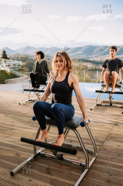 Content people sitting on pilates chairs and practicing with dumbbells while smiling and looking away