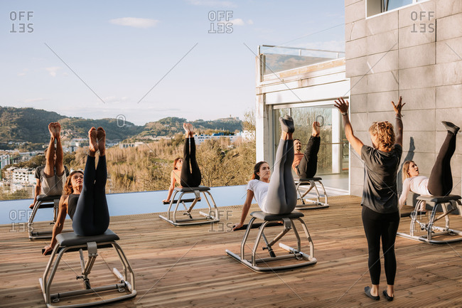 Company of people in sportswear doing abs exercises on pilates chair during training on terrace on sunny day