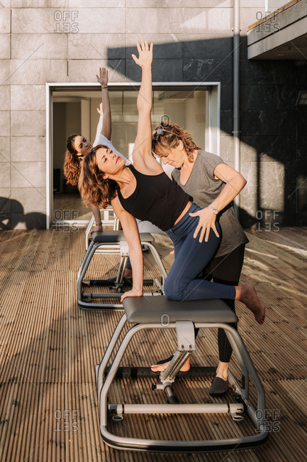 Side view of slim woman doing exercises on pilates chair with help of professional coach while stretching arms during training on terrace