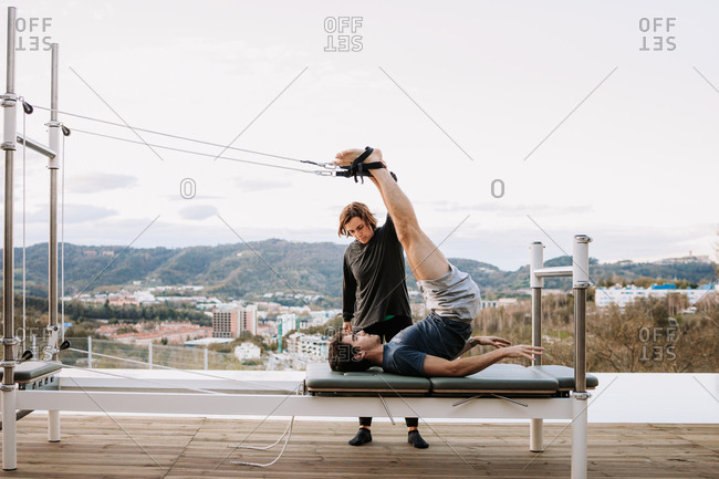 Calm male in activewear lying on pilates cadillac and stretching legs with straps under supervision of personal female coach on terrace