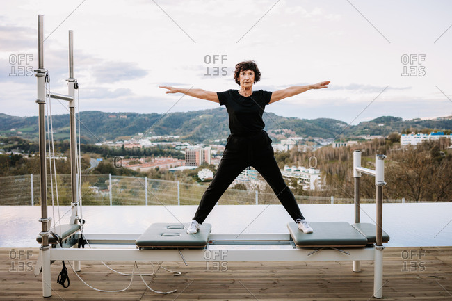Middle aged female in sportswear standing with outstretched arms on pilates reformer and balancing during training on terrace