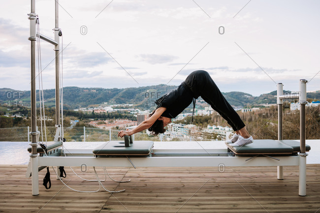 Side view of graceful female doing yoga in Eka Pada Adho Mukha Svanasana on pilates reformer on terrace at sunset