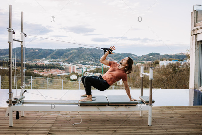 Side view of flexible male standing in Urdhva Dhanurasana with straps on pilates machine and stretching body while practicing yoga on terrace