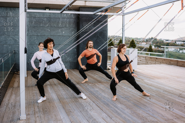 Group of people in sportswear leaning on straps and practicing yoga in Parivrtta Adho Mukha Svanasana on wooden terrace
