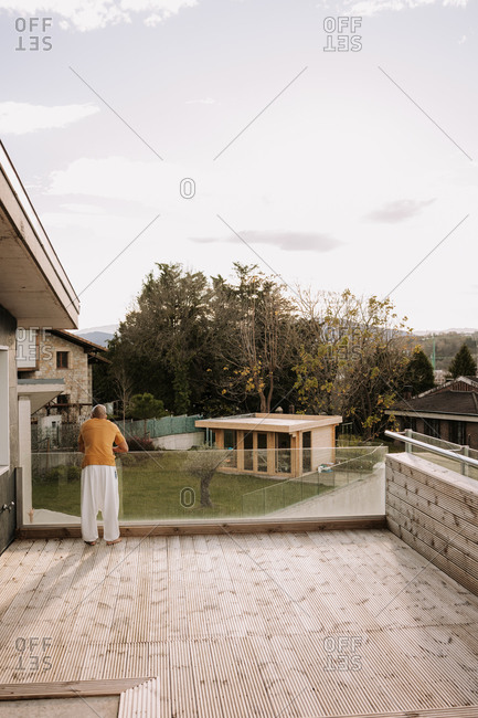 Back view of unrecognizable male leaning on glass fence while standing on wooden terrace of luxury contemporary house
